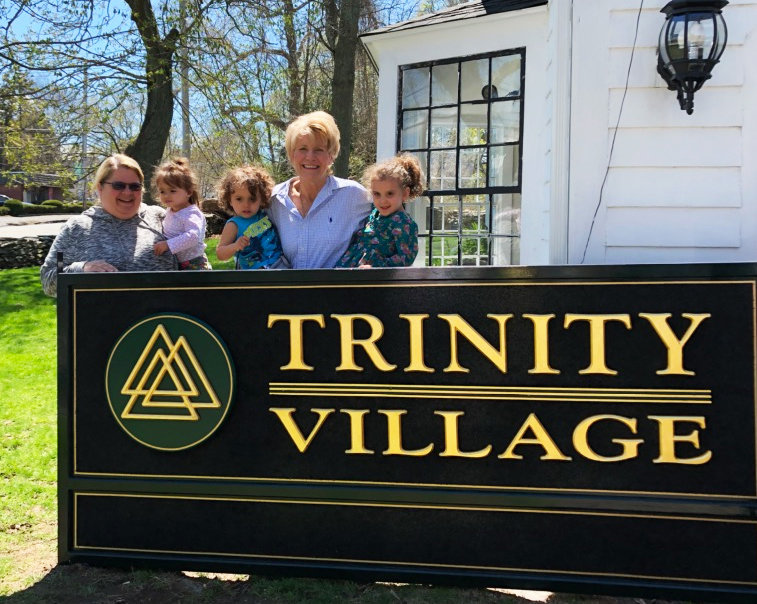 Holly Cekala, left, and Christine Nolan, fourth from left,  the CEO of Trinity Village, prepare to hang the sign for The Blessing Way.