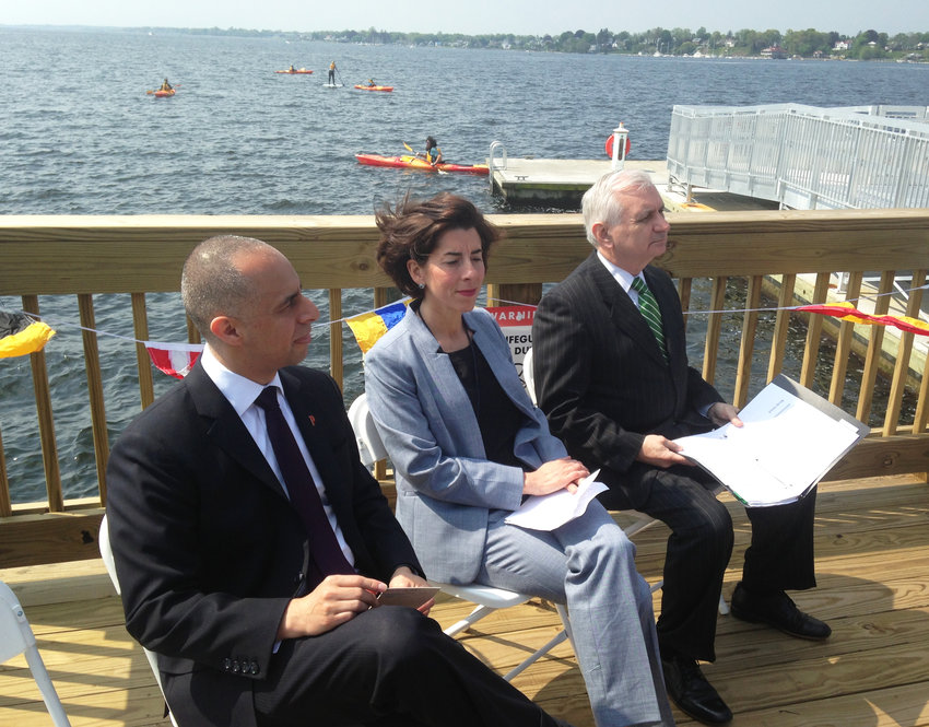 Mayor Jorge Elorza, Gov. Gina Raimondo, and Sen. Jack Reed at the ribbon-cutting at the new Save the Bay dock facilities at its Fields Point headquarters,with paddle boarders and kayakers behind them.