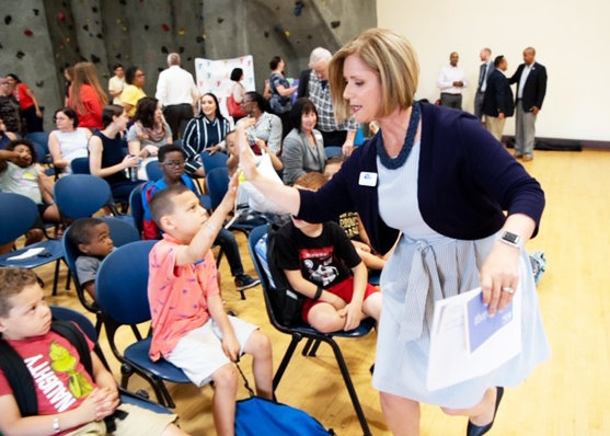 Cortney Nicolato, president and CEO of United Way of Rhode Island, high fives a member of the summer learning initiative celebration.