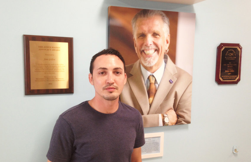 Jonathan Goyer, in front of a portrait of Jim Gillen.