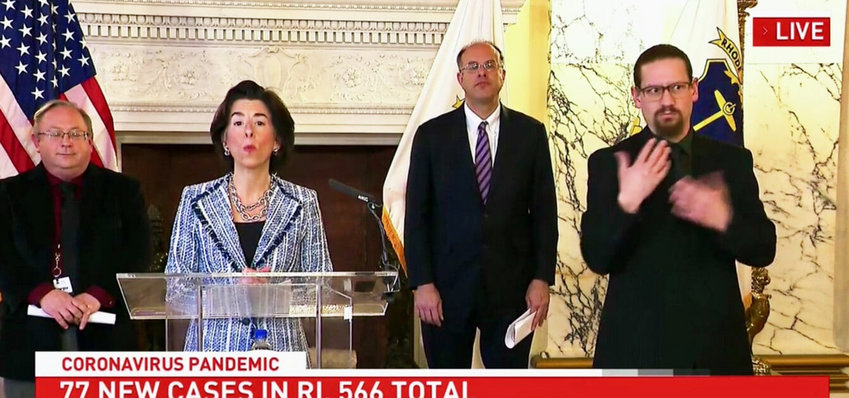 A daily news briefing by Gov. Gina Raimondo. From left, Dr. James McDonald, R.I. Department of Health; the Governor; Commerce Corp. Secretary Stefan Pryor; and the sign language interpreter.