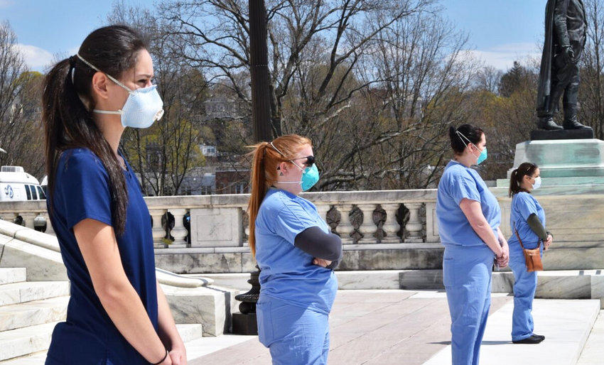Health workers confront protesters at the State House on Saturday, April 25.