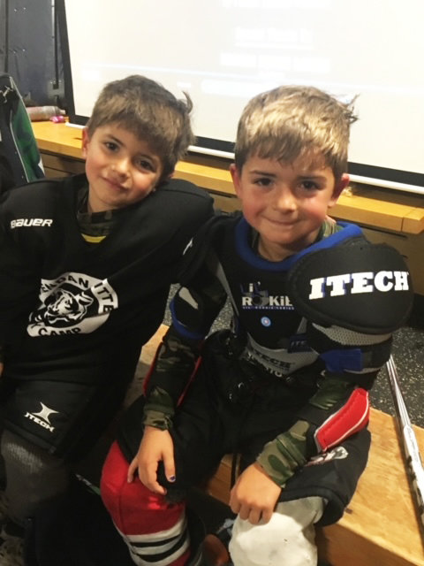 Zach Simon, left, and Cam Simon, from an earlier youth hockey event before COVID.  Today, all players, coaches, and parents are masked, on the rink and off the rink before and after games.