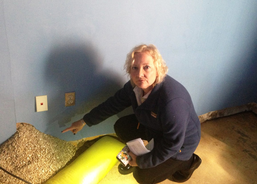 Karen Rathbun, vice president of administrative services at Community Care Alliance in Woonsocket, points to a hole in the wall with insulation pouring out, caused by water damage from a leak in the roof at the state-owned building, which was identified in 2017 but never repaired by the R.I. Department of Administration, leading to unhealthy conditions, including black mold, forcing the agency to move to temporary offices.