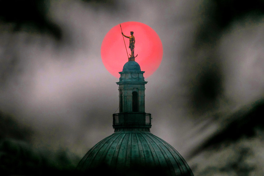 The Independent Man atop the Rhode Island State House framed by a reddened sun, tinted by the smoke from forest fires in the American West.