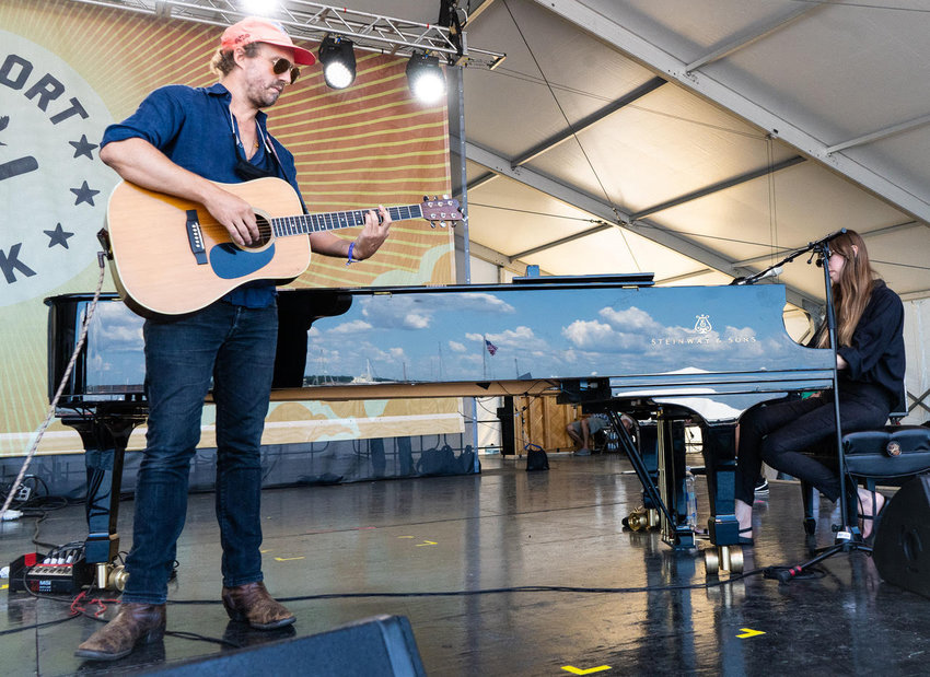 Matthew Houck performs as Phosphorescent at the 2021 Newport Folk Festival, with the sky reflected on the piano.