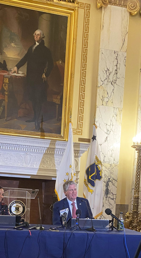 Gov. Dan McKee at a news conference at the State House, underneath the portrait of George Washington.