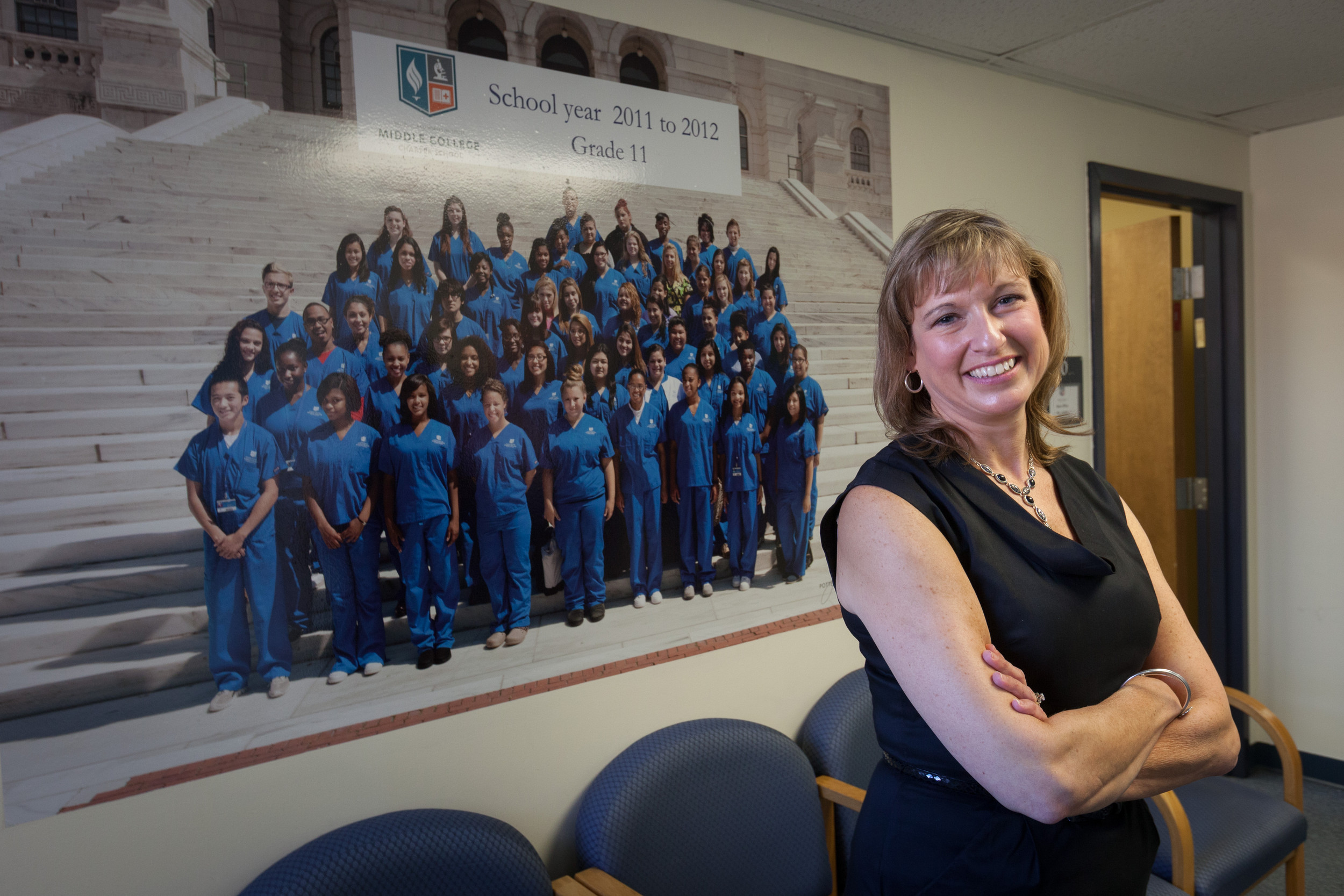 Pamela McCue, CEO of the R.I. Nurses Institute Middle College Charter School, in front of a poster of the first entering class of students from 2011.