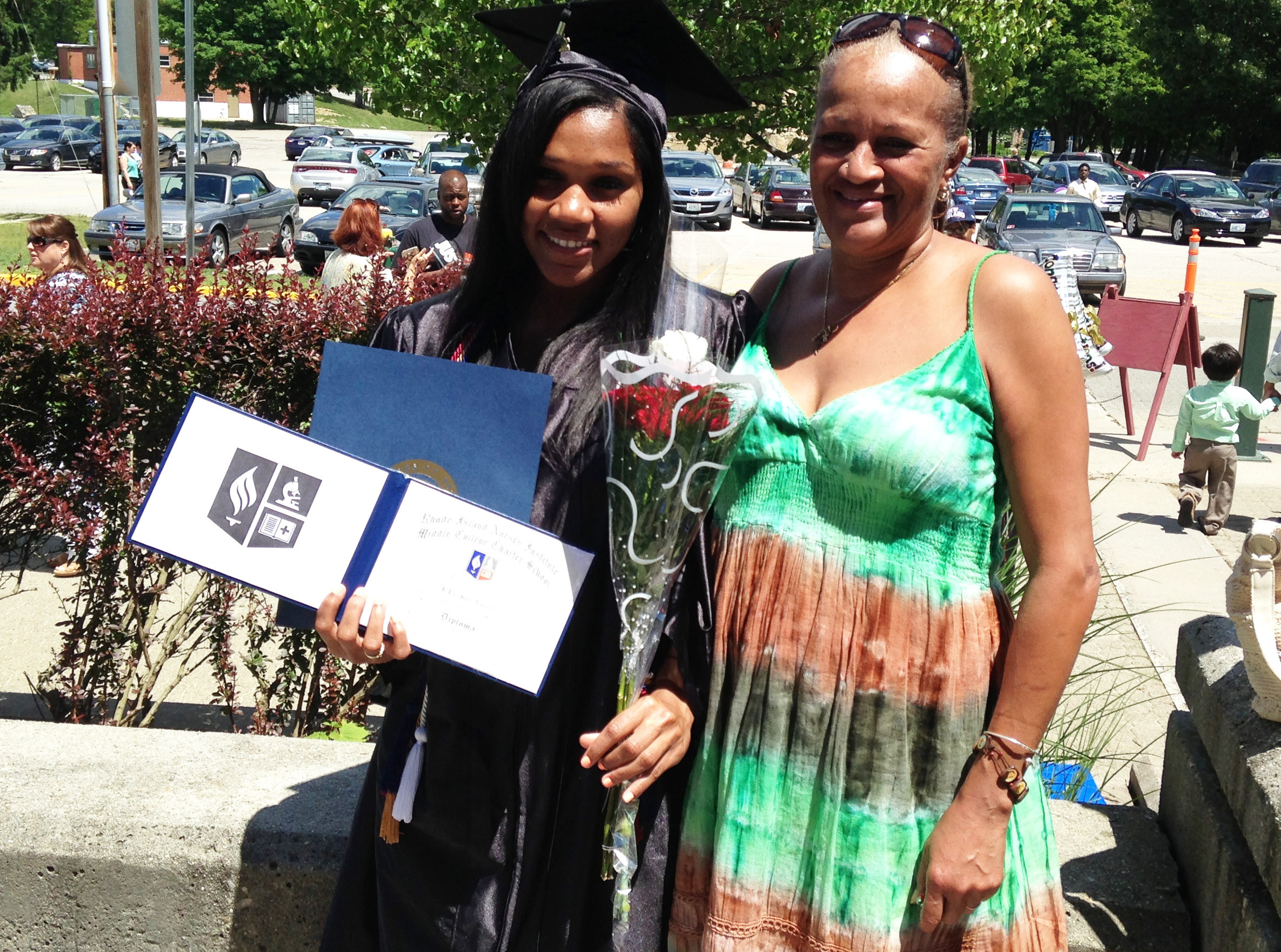 A new graduate of RINI-MC poses with the grandmother and her diploma.