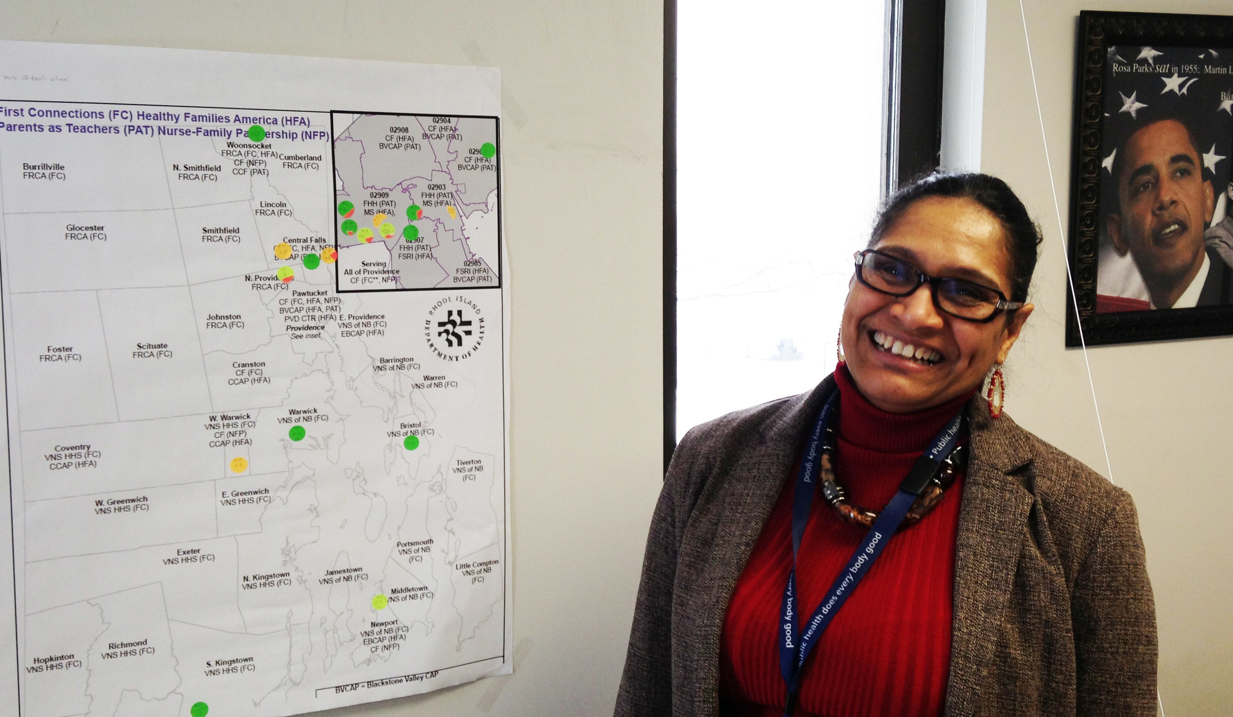 Ana Novais, the executive director of the division of Community, Family Health and Equity at the R.I. Department of Health, in front of a map of Rhode Island showing where the 11 Health Equity Zones will be located.