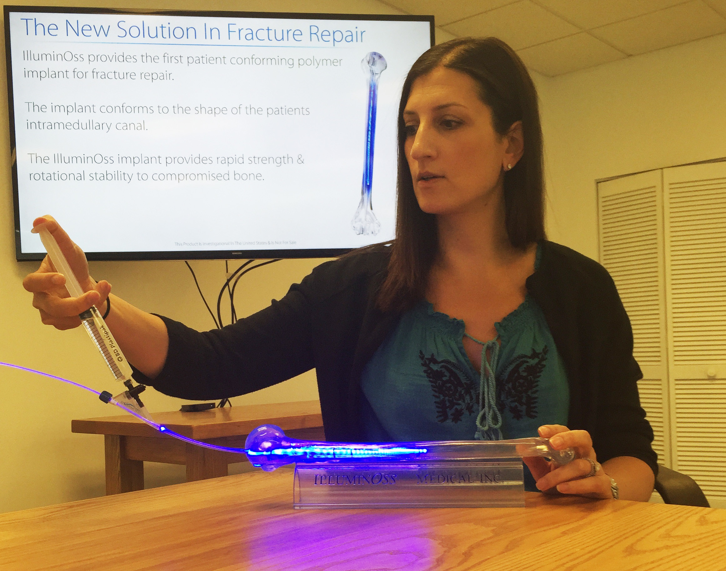 Amy Berman, vice president of clinical affairs, demonstrates IlluminOss's new technology to repair bone fracture.