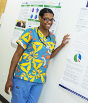 Valerie Joseph, full-time nurse director of Clinica Esperanza, wears one of the colorful scrubs that have become part of the HPV prevention campaign at the clinic. The bold blue and yellow print displays uteruses surrounded by a near-invasion of HPV viruses in abnormal cancer cells.