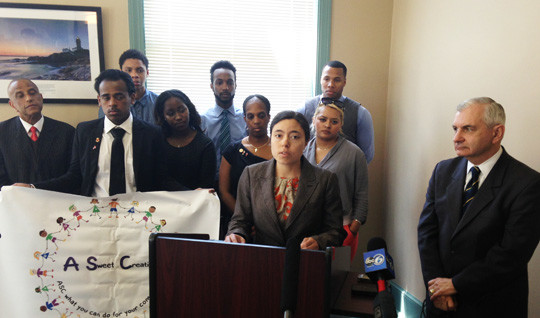 Laura Brion, center, with the Childhood Lead Action Project, addresses the May 23 news conference. Sen. Jack Reed is at the right, with the students from the Providence NAACP Youth Council standing behind.