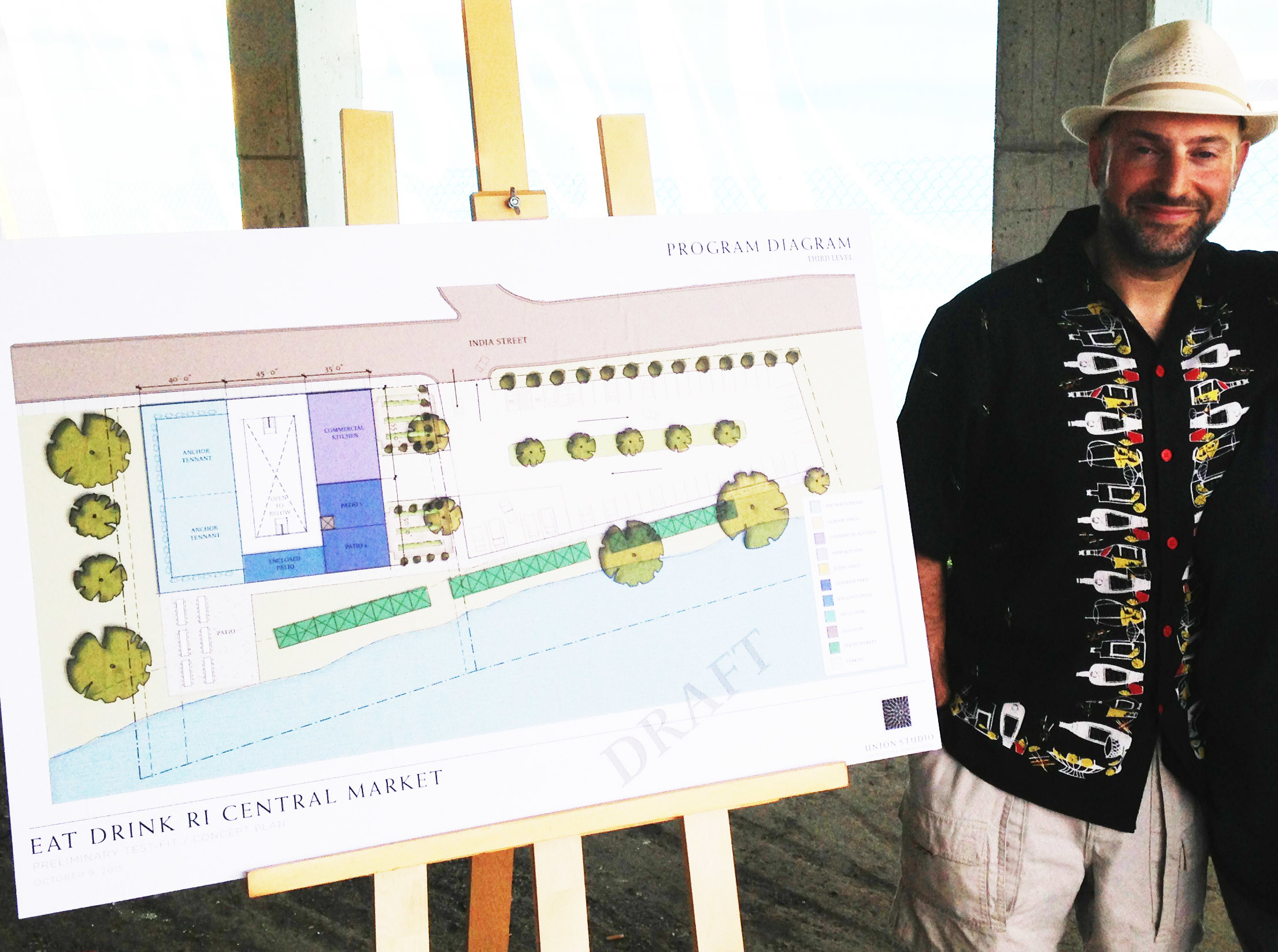 David Dadekian of Eat Drink RI, at the pop up market held on Aug. 6 to support the plans to build a Central Market as a hub for Rhode Island food entrepreneurs on the Providence waterfront, next to the draft architectural plans.
