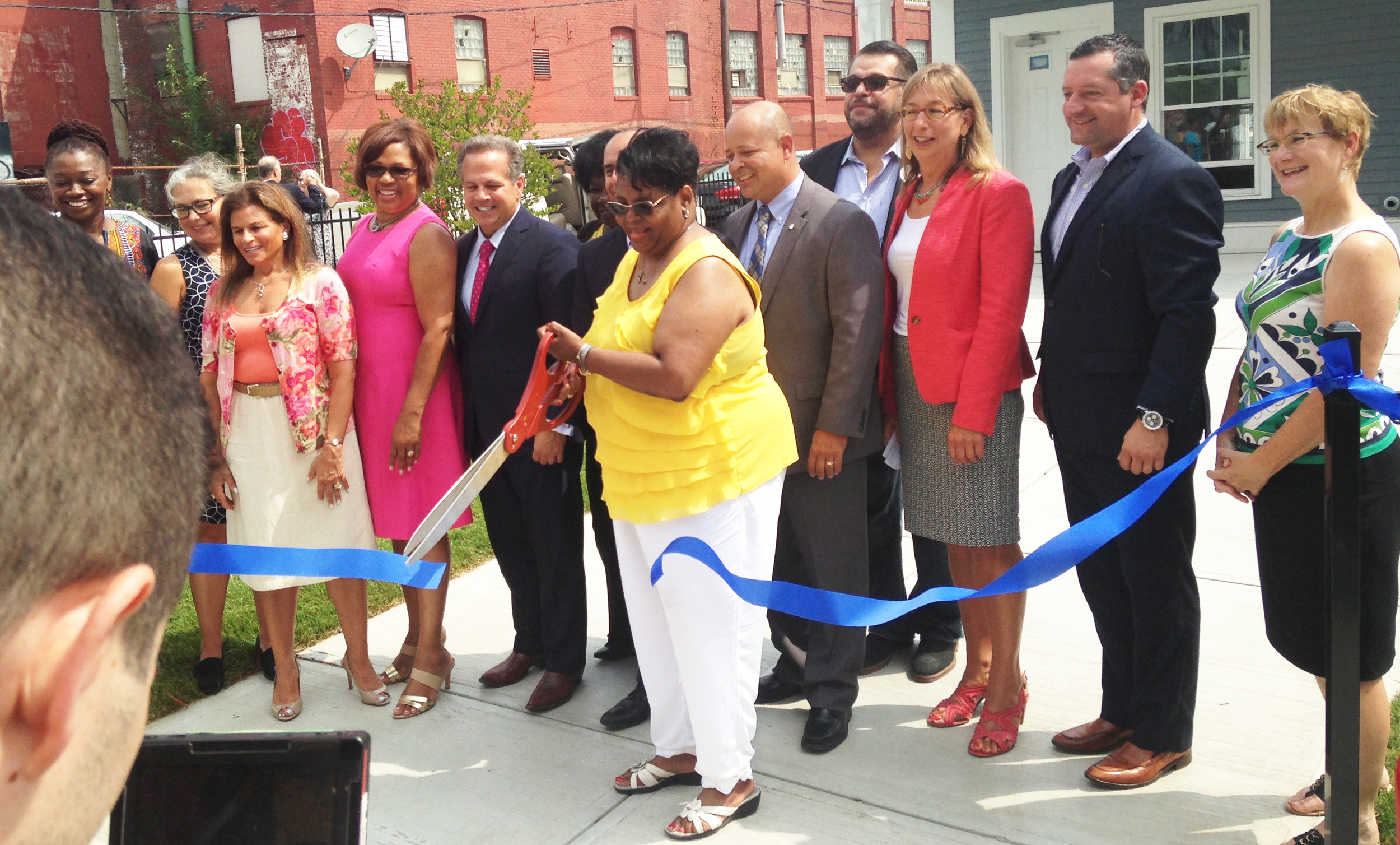 Sharon Conard-Wells of West Elmwood Housing Development Corporation cuts the ribbon to celebration the completion of a new 50 units of affordable housing, surrounded by supporters, investors and officials.