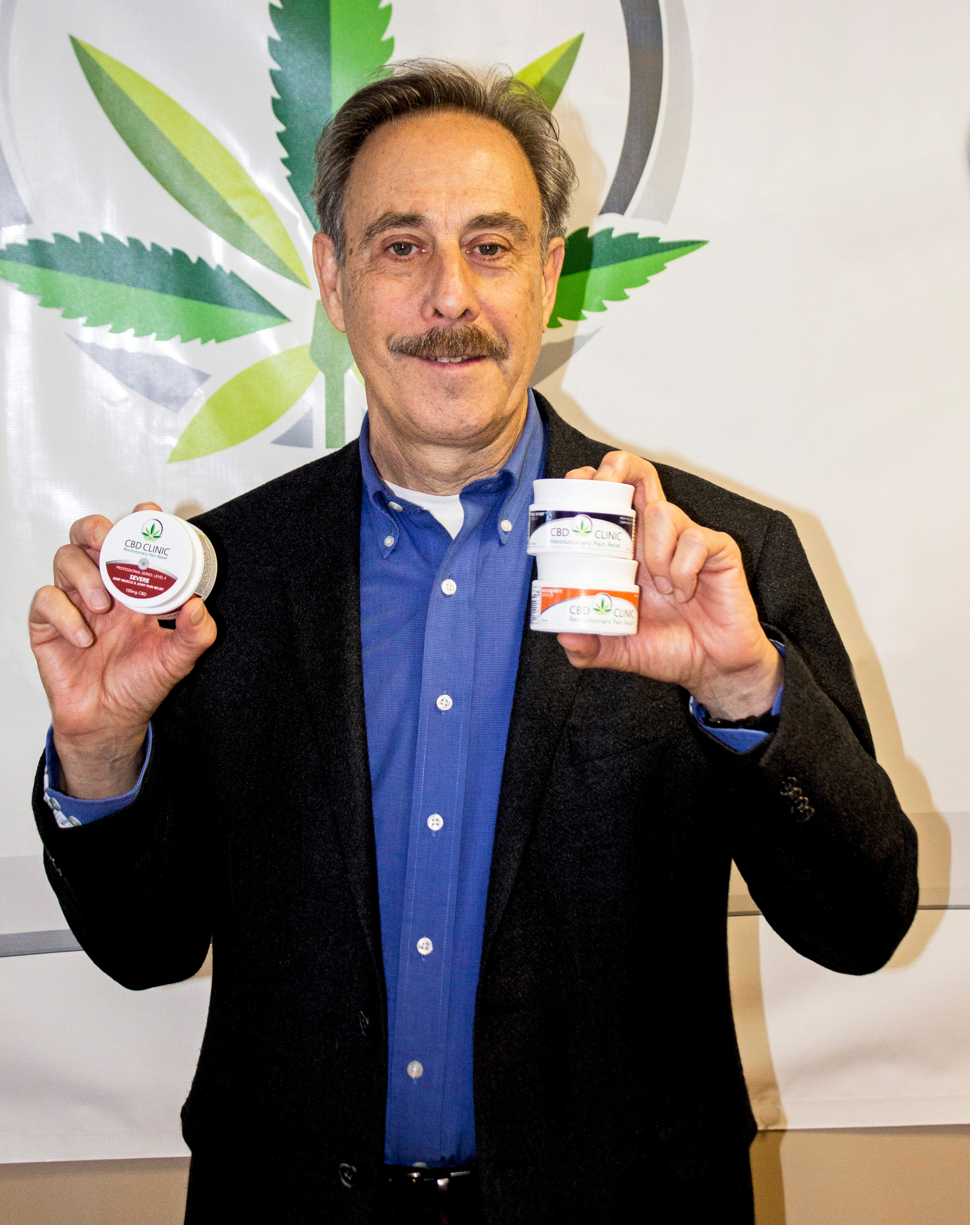 David Goldsmith, whose firm, CBD Clinic, has developed a new, non-prescription topical product to help relieve chronic pain, using CBD extract from marijuana, proudly displaying jars of his new product.