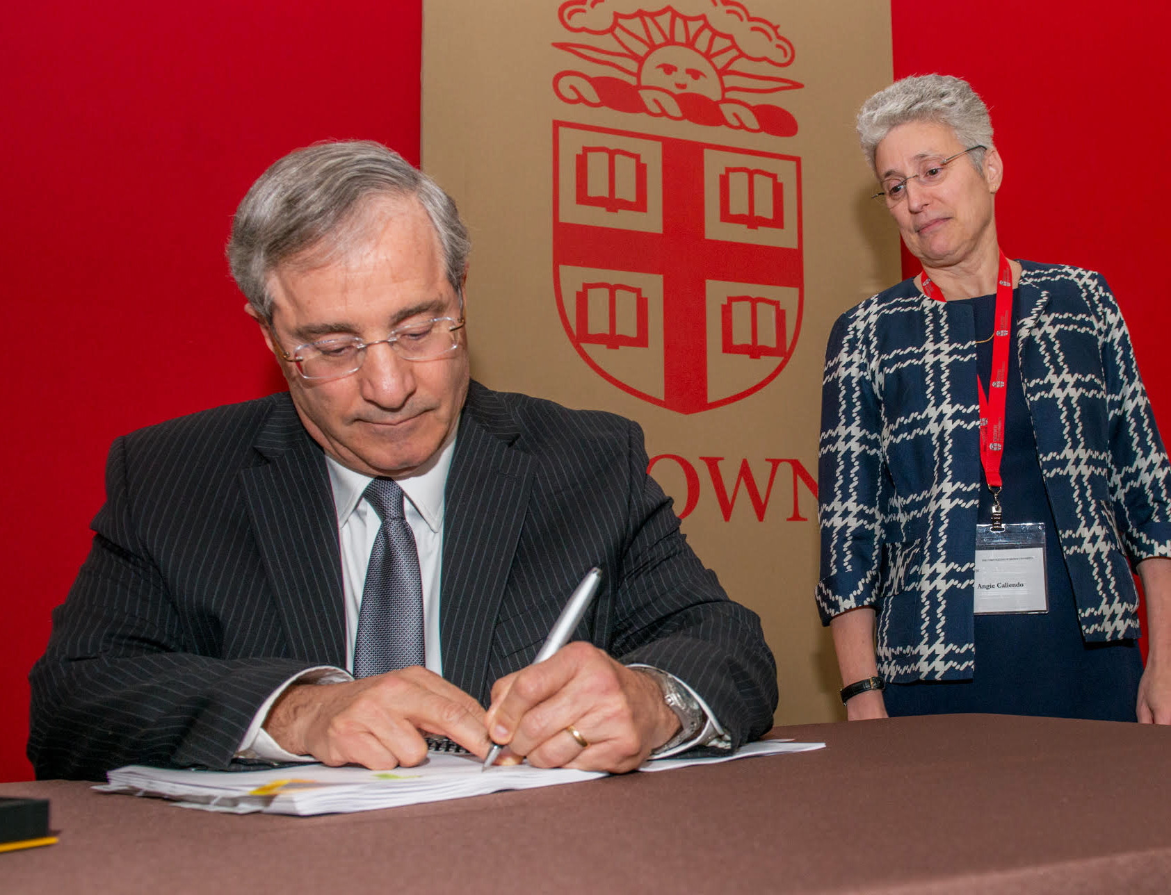 Dr. Jack A. Elias, senior vice president for Health Affairs and dean of Medicine and Biologic Sciences at Brown University, signs a new agreement creating Brown Physicians, Inc., as Dr. Angela Caliendo, vice president of University Medicine Foundation and interim executive director of Brown Physicians, Inc., looks on.