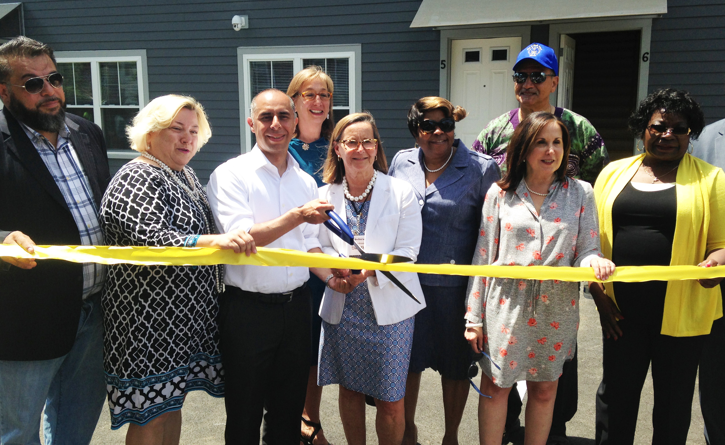 Providence Mayor Jorge Elorza, holding the scissors, cuts the ceremonial ribbon at the opening of the 841 Broad Street mixed used development.