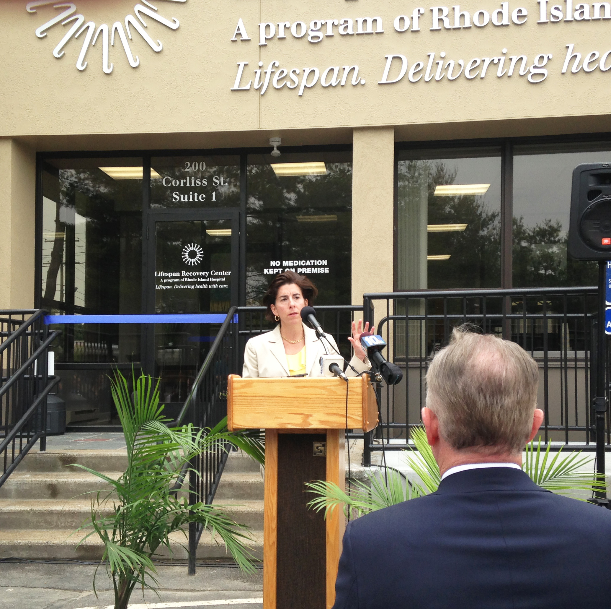 Gov. Gina Raimondo talks at the opening of the new Lifespan Recovery Center on June 19, as Dr. Timothy Babineau, president and CEO of Lifespan, listens attentively.