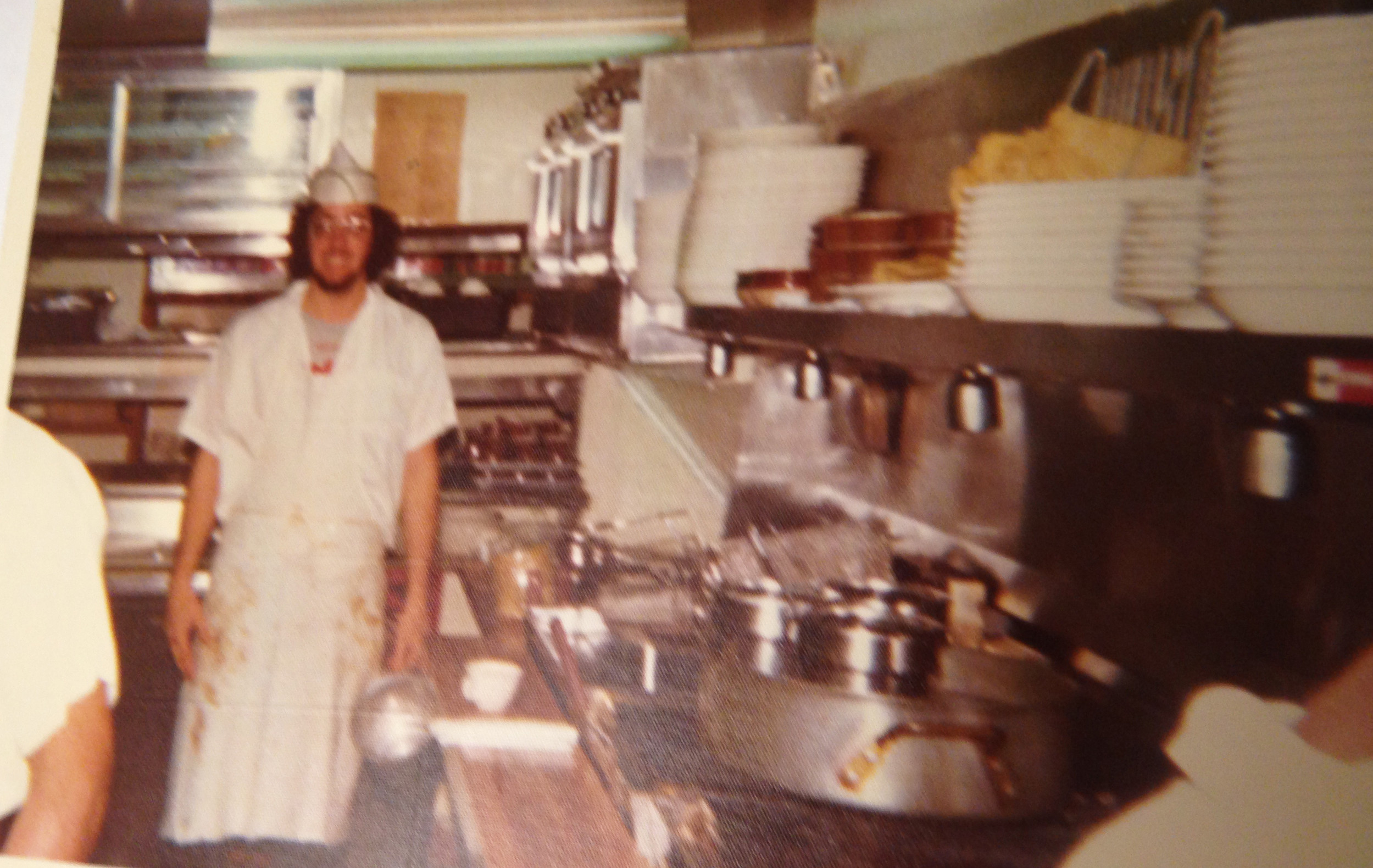 A blurry portrait of a young man as a cook in the basement kitchen at Rocky Raccoon's Saloon in 1975 in Washington, D.C.