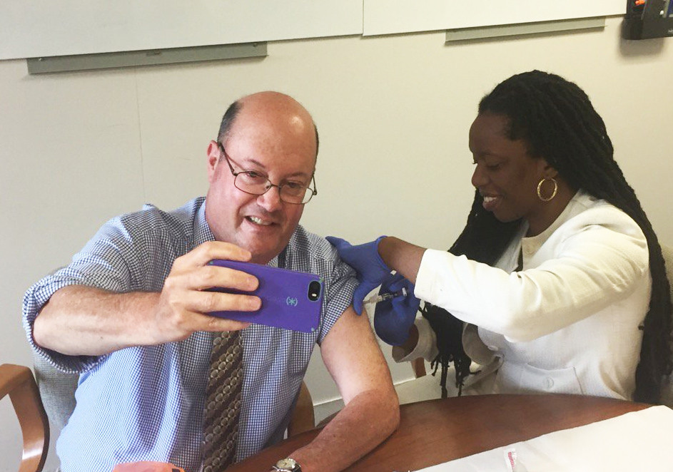 With Dr. Nicole Alexander-Scott delivering a flu shot, Steve Klamkin of WPRO pulls off the extremely rare vaccination selfie, as part of the the R.I. Department of Helath's annual flu vaccine kickoff on Sept. 25.