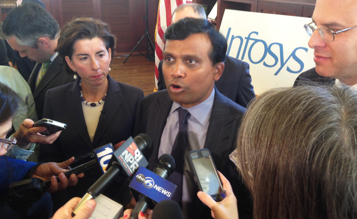 Ravi Kumar, center, president of Infosys, talks with reporters following the Nov. 27 announcement that the global company will be locating a new design and innovation hub in Providence, creating 500 new jobs, as Gov. Gina Raimondo, left, and CommerceRI Secretary, Stefan Pryor, right, listen.