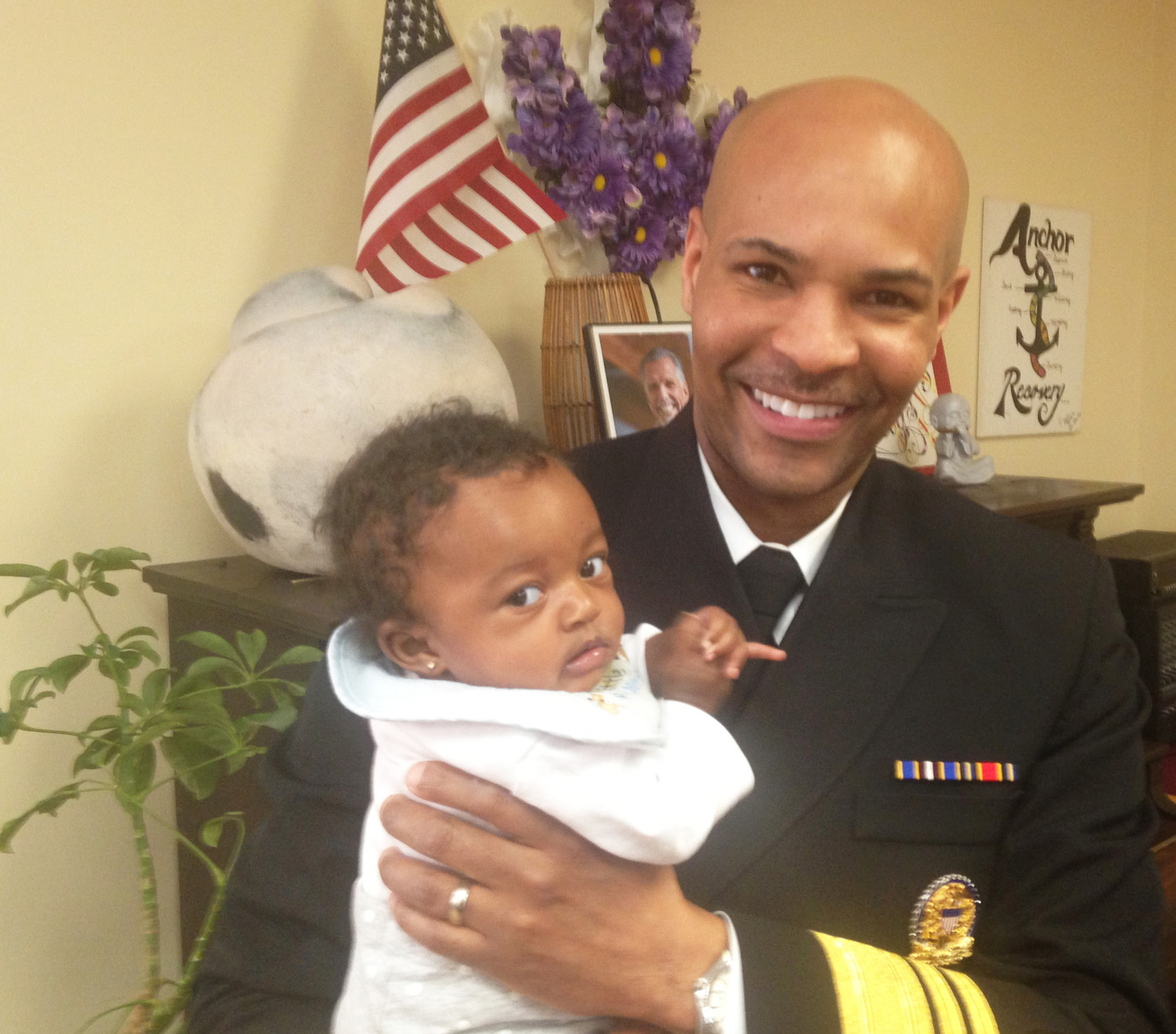 U.S. Surgeon General Dr. Jerome Adams holding a young baby girl during an interview at the Anchor Recovery Community Center on Jan. 26. Above his shoulder is the photograph of a smiling Jim Gillen, one of the leaders of the recovery community in Rhode Island.