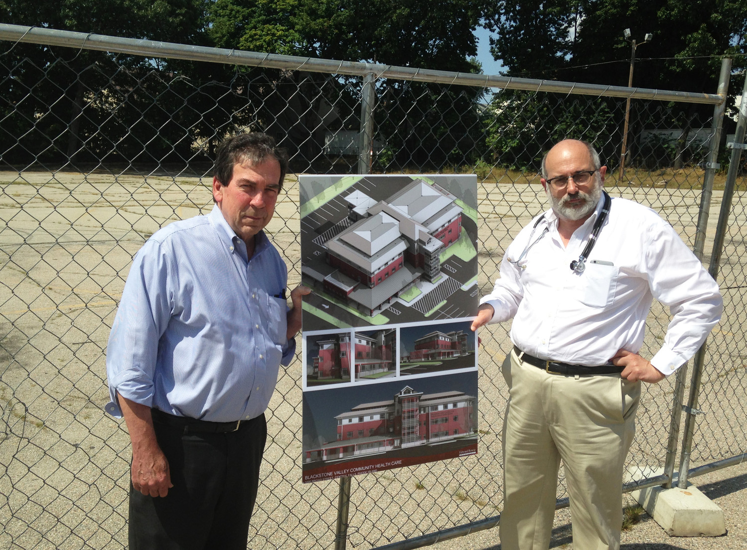 Ray Lavoie, left, and Dr. Michael Fine, at the site of the new Neighborhood Health Station in Central Falls, in August of 2017, holding architectural renderings of the new facility.