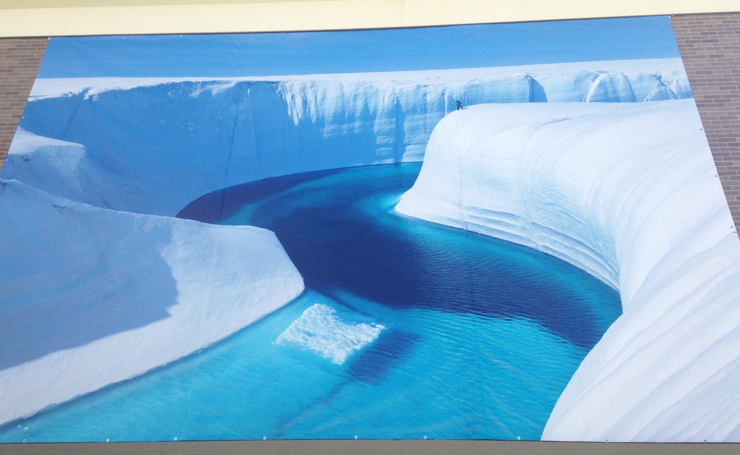 A large public mural, from the photographer by James Balog, attached to the brick facade of the School of Engineering at Brown University, portraying Birthday Canyon and the melting of the Greenland ice sheet.