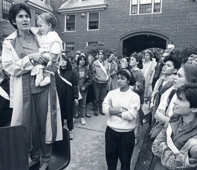 Toby Simon, left, holding her son, Ben, and speaking at a 1985 rally at Brown University calling for an end to sexual assault. The students had deliberately chosen to hold the rally in Wriston Quad, where most the fraternities were located, according to Simon.