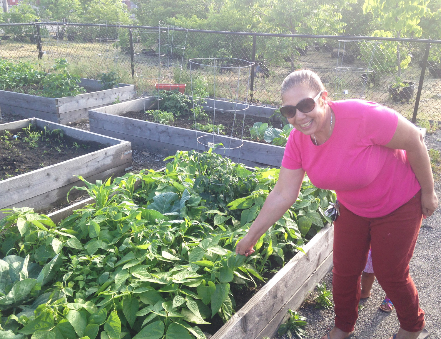 A tenant proudly displays her bountiful raised growing bed of vegetables as part of the Sankofa Initiative.