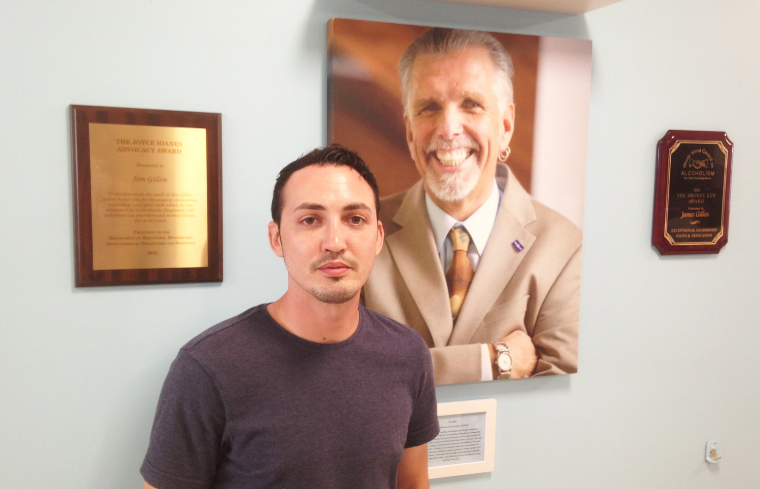 Jonathan Goyer, community recovery advocate, in front of a portrait of Jim Gillen.