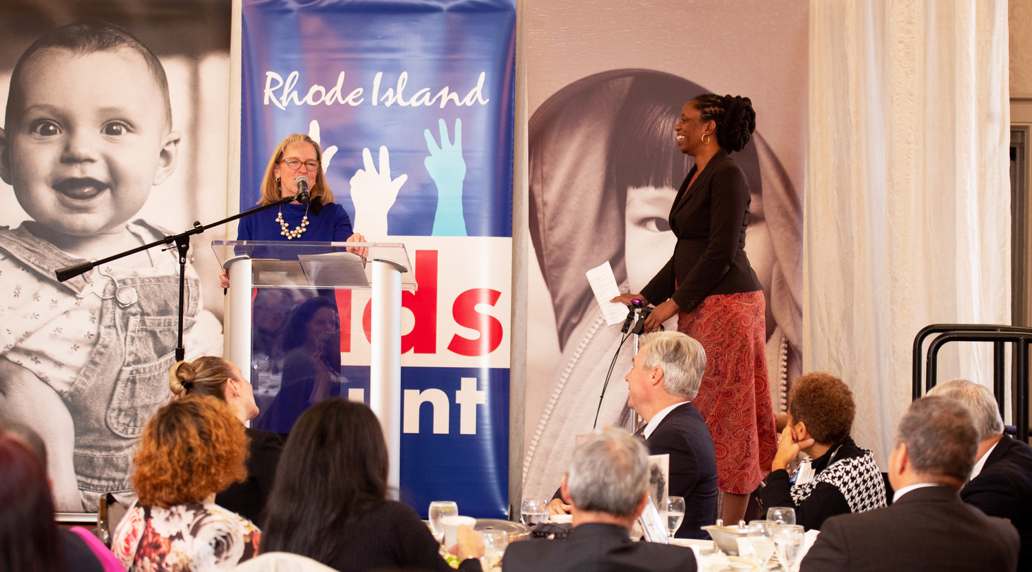 Elizabeth Burke Bryant welcomes Dr. Nicole Alexander-Scott, on her scooter, to speak at the Rhode Island Kids Count annual luncheon celebrating children in November of 2018.