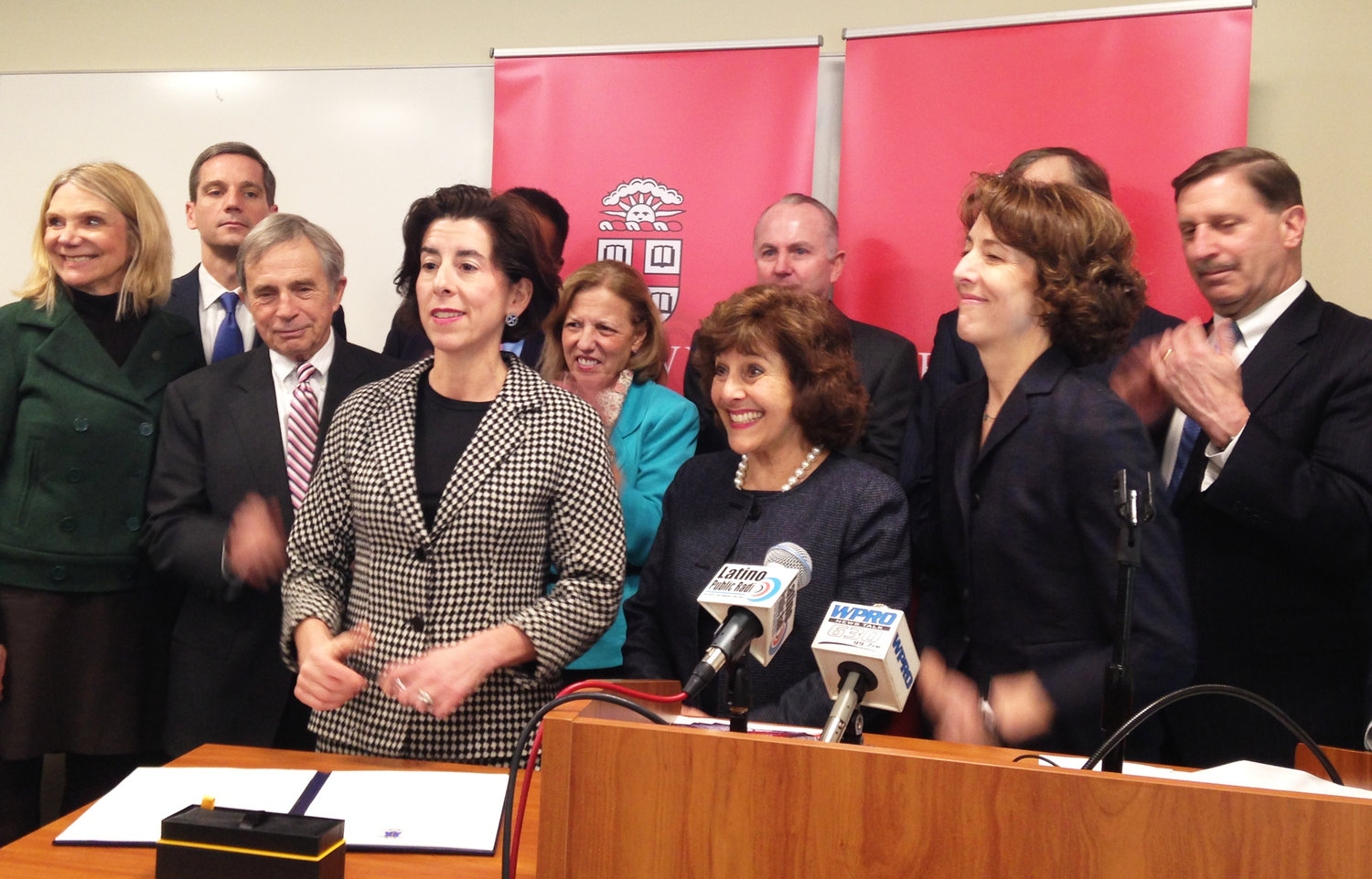 Gov. Gina Raimondo signs an executive order placing a voluntary cap of the annual growth of health care spending at 3.2 percent.