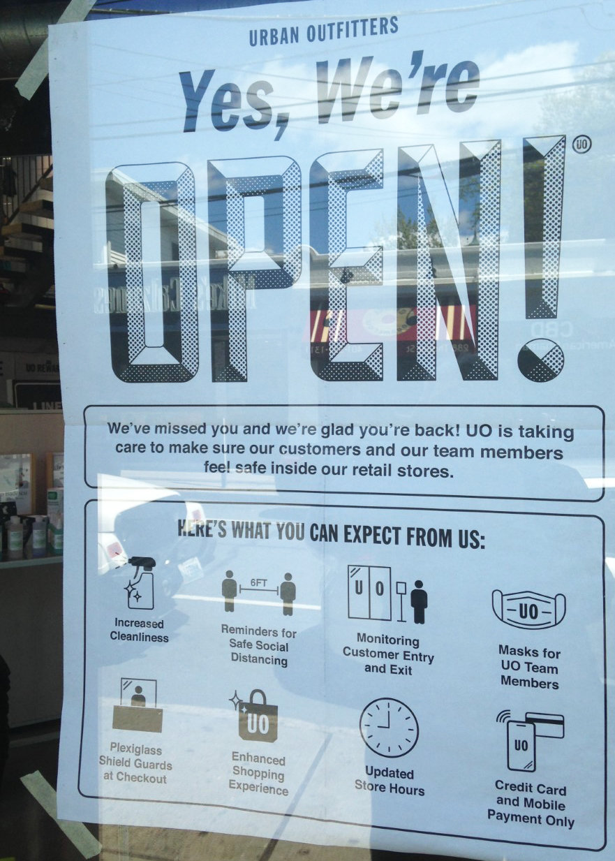 The sign in the window at Urban Outfitters on Thayer Street in Providence, announcing that the retail store is open for business again.
