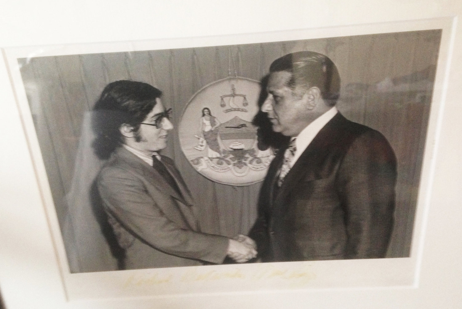 A photograph of Mayor Frank Rizzo shaking hands in front of the seal of Philadelphia at City Hall in 1973.