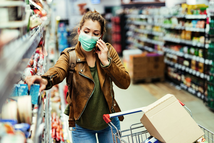 Young woman wearing protective face mask while buying groceries and talking on the phone during coronavirus pandemic in the supermarket.