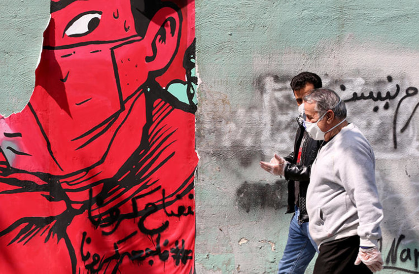 Iranians wearing protective mask walk past graffiti on a wall in Tehran on April 13, 2020 during the coronavirus COVID-19 pandemic. - Iran's health ministry today reported another 111 deaths from the novel coronavirus, taking the official overall toll in the worst-hit Middle East country to 4,585. Ministry spokesman Kianoush Jahanpour said 1,617 new infections took the total number of cases in the country's outbreak to 73,303, of whom 45,983 had recovered. (Photo by ATTA KENARE / AFP)