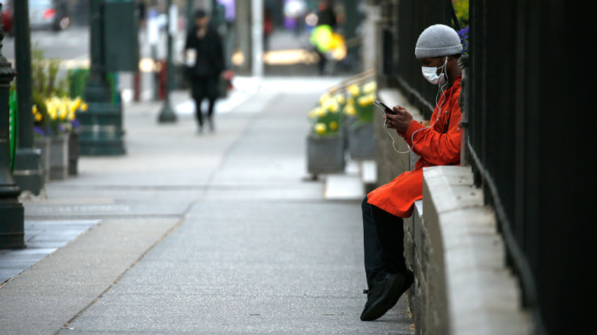 NEW YORK NY, - APRIL 12:  A man wearing a protective mask looks at his portable telephone on 6th Avenue amid the coronavirus pandemic on April 12, 2020 in New York City. COVID-19 has spread to most countries around the world, claiming over 114,000 lives with infections at over 1.8 million people. (Photo by John Lamparski/Getty Images)