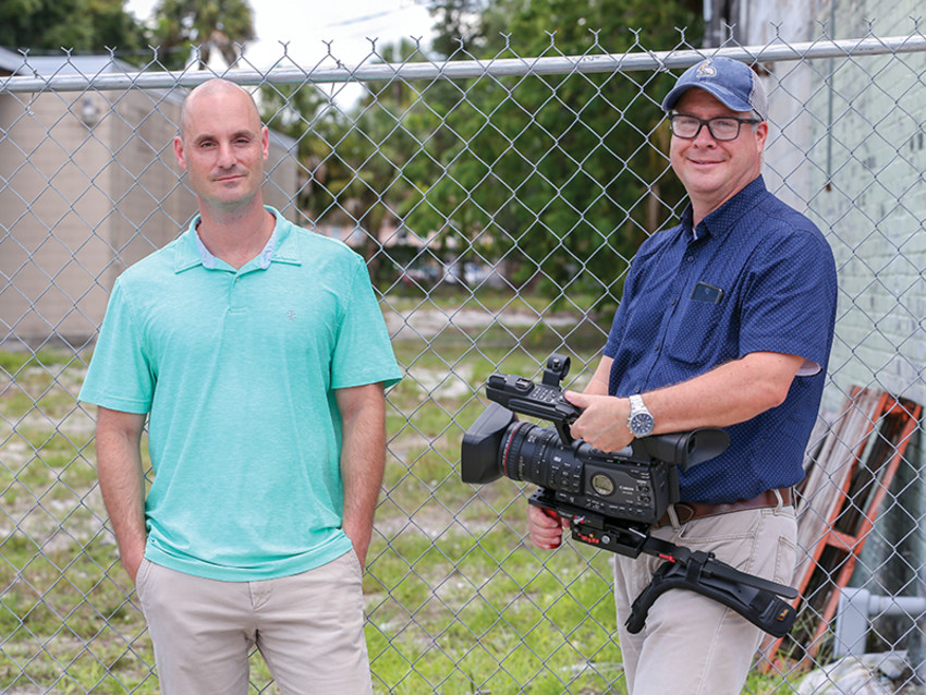 General assignment reporter Paul Guzzo (left) and video producer James Borchuck stand in front of what was once Zion Cemetery. (Photo provided)