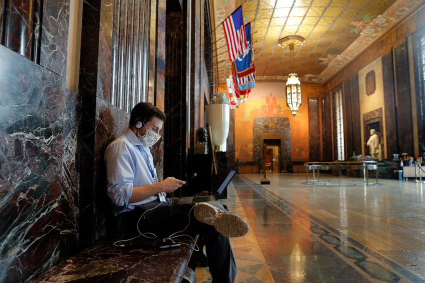 Harrison Golden, a reporter for WVLA television station, sits alone wearing a mask as he reports outside  the Louisiana state senate chamber in Baton Rouge, La., Monday, May 4, 2020. With some in masks and others uncovered, Louisiana lawmakers Monday resumed the final four weeks of a legislative session stalled by the coronavirus, trying to get their arms around the scale of the budget problems caused by the outbreak. The return to the Capitol has caused a new rift between Republicans, who hold the majority and pushed for a restart of work, and Democrats who said it was too risky to have hundreds of people in the building in a state that is one of the nation's hot spots for the COVID-19 disease caused by the virus.(AP Photo/Gerald Herbert)