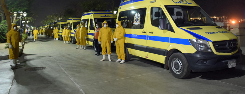 """Egyptian health ministry emergency responders stand next to ambulances ready on the scene to transport suspected COVID-19 coronavirus disease cases that were detected on a Nile cruise ship, in the southern city of Luxor late on March 7, 2020. - Egypt's health ministry said the 45 detected cases would be quarantined even though 11 of them had tested negative in follow-up tests. The """"A Sara"""" docked in Luxor days after authorities were alerted that a foreign tourist who had previously disembarked had contracted the virus and infected others onboard. (Photo by - / AFP) (Photo by -/AFP via Getty Images)"""