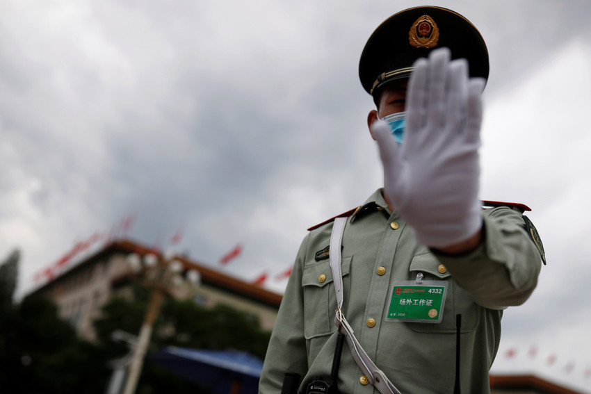 A paramilitary police officer, wearing a mask following the coronavirus disease (COVID-19) outbreak, gestures at the photographer outside the Great Hall of the People after the second plenary session of the National People's Congress (NPC) in Beijing, China May 25, 2020. REUTERS/Thomas Peter - RC2MVG9L5ZKM
