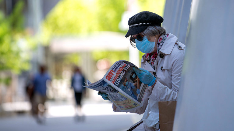 NEW YORK, NEW YORK - MAY 21: A woman wearing a mask and gloves reads a local newspaper amid the coronavirus pandemic on May 21, 2020 in New York City. COVID-19 has spread to most countries around the world, claiming over 334,000 lives with over 5.1 million cases. (Photo by Alexi Rosenfeld/Getty Images)