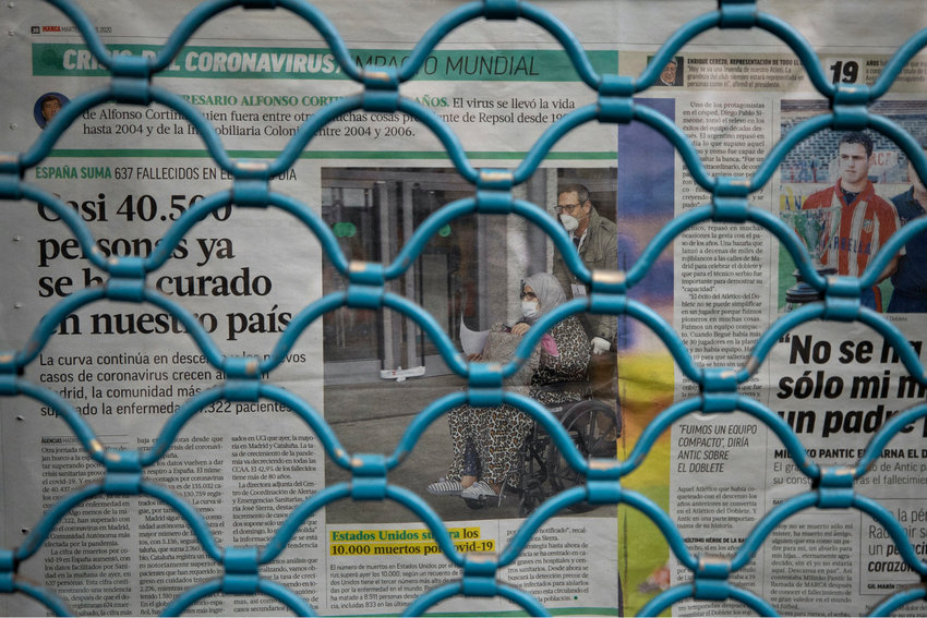 Newspapers are seen covering a window behind a closed shutter of a bar as the lockdown to combat the spread of coronavirus continues in Madrid, Spain, Friday, April 10, 2020. Spain's parliament has endorsed a government request to extend by two more weeks the current state of emergency. Strict rules that keep people at home except for shopping for food and medicine and the shutting down of all non-essential industry have helped Spain reduce its daily rate of contagion growth. The COVID-19 coronavirus causes mild or moderate symptoms for most people, but for some, especially older adults and people with existing health problems, it can cause more severe illness or death.(AP Photo/Paul White)..