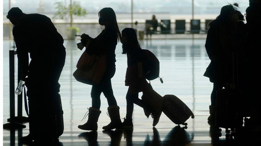 Travelers walk through the Salt Lake City International Airport Wednesday, March 17, 2021, in Salt Lake City. (AP Photo/Rick Bowmer)