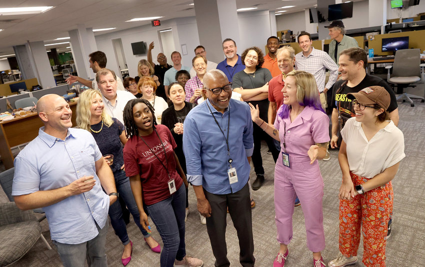 Michael Paul Williams, center, a columnist for the Richmond Times-Dispatch, celebrates with other newsroom staff at the newspaper, Richmond, Va., Friday, June 11, 2021 after earning a Pulitzer Prize in Commentary for his work in 2020..