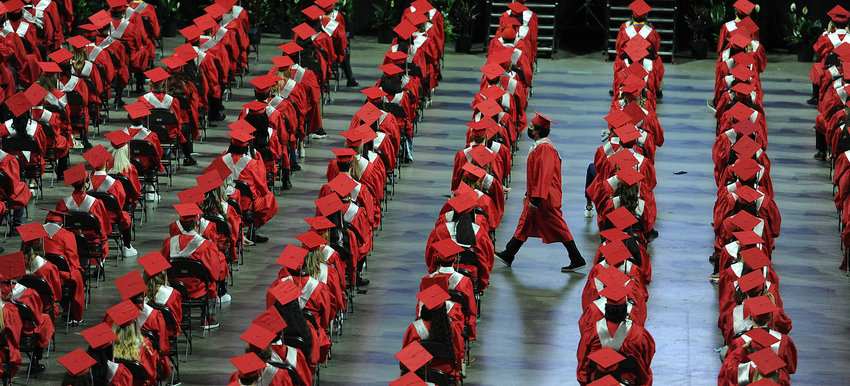 Illinois' Palatine High School students attend their 138th commencement held at the NOW Arena in Hoffman Estates, Ill. as one student running late hustles to his seat.