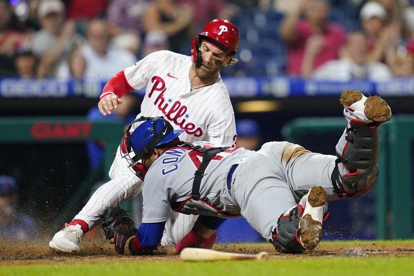 Philadelphia Phillies' Bryce Harper, left, scores past Chicago Cubs catcher Willson Contreras during the sixth inning of a baseball game, Sept. 14, 2021, in Philadelphia. (Photo by Matt Slocum/AP)