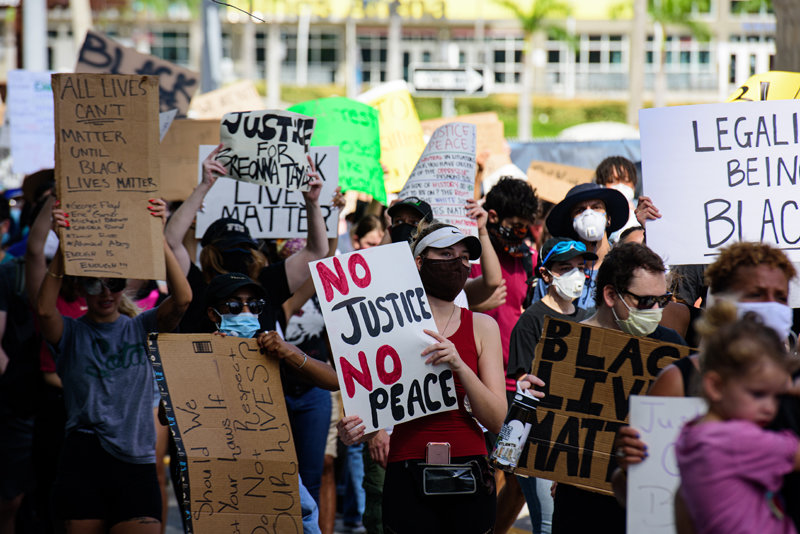 Miami Downtown, FL, USA - MAY 31, 2020: People. White and black together on demonstrations. No justice no peace poster in woman hands. All lives cant matter sign. Against the murder of George Floyd